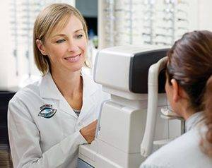 Optometrist giving patient eye exam
